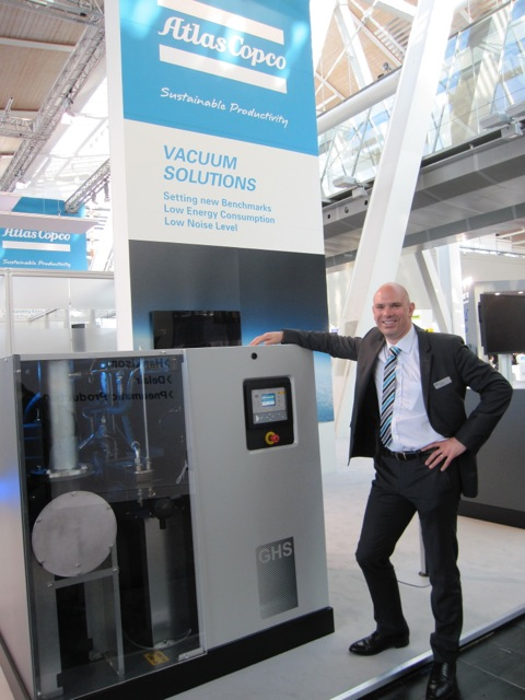 Conrad Latham, from Atlas Copco, next to the GHS 1900VSD 37 kW rotary screw vacuum pump for 0,35 mbar with the standard low-sound enclosure